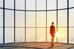 New day new opportunities. Back view of businesswoman in modern office facing sunrise Stock Photos