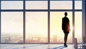 New day new opportunities. Back view of businesswoman in modern office facing sunrise Stock Image