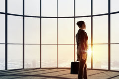 New day new opportunities. Back view of businesswoman in modern office facing sunrise Royalty Free Stock Photography