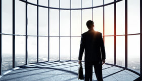 New day new opportunities. Businessman standing in office and looking on sunrise in window Royalty Free Stock Photo