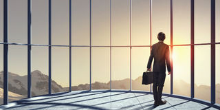 New day new opportunities. Businessman standing in office and looking on sunrise in window Stock Images
