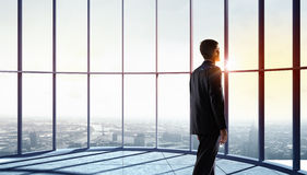 New day new opportunities. Businessman standing in office and looking on sunrise in window Royalty Free Stock Images