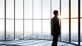 New day new opportunities. Businessman standing in office and looking on sunrise in window Royalty Free Stock Photos