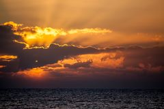 New day. Ocean dawn horizon with sun breaking behind cloud. Stock Photo