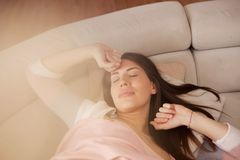 New day start. Sleepy woman stretching on sofa stock photography