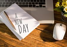 A New Day text written on page with laptop royalty free stock images