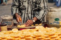 New Dehli, Índia, o 19 de fevereiro de 2018: O homem prepara o abacaxi para a venda foto de stock royalty free