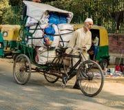 New Dehli, Índia, o 19 de fevereiro de 2018: Homem que leva a carga maciça no bic Fotos de Stock Royalty Free
