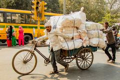 New Dehli, la India, el 19 de febrero de 2018: Hombre que lleva la carga masiva en el Bic imágenes de archivo libres de regalías