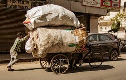 New Dehli, la India, el 19 de febrero de 2018: Hombre que lleva la carga masiva en el Bic Fotografía de archivo