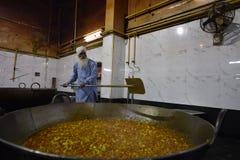 New Delhi, Inde, le 23 novembre 2017 : Un homme préparant la nourriture dans un grand pot pour de pauvres personnes à l'intérieur Photo libre de droits
