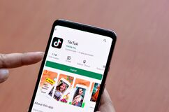 Free New Delhi, India, 2020. Woman Installing TikTok Mobile App On A Smartphone Screen With A Wooden Background Depicting Logo Of Royalty Free Stock Photos - 183541438