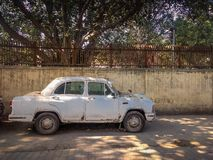 New Delhi, India - April 25, 2019. A Old White Ambassador car is parked on a street royalty free stock photo