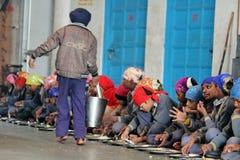 Free NEW DELHI, INDIA - March 21, 2019 : Pilgrims Eat Free Meals In The Golden Temple Gurudwara Bangla Sahib In Delhi Stock Photo - 142973910