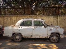 New Delhi, India - April 25, 2019. A Old White Ambassador car is parked on a street stock image