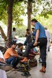 New Delhi Indien - April 10, 2016: Skor för Unidentifie yrkesmässiga gatasopare med kunder i New Delhi Royaltyfri Foto