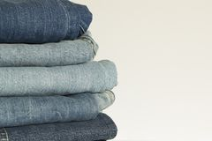 New denim pants clothes pile background. Stack of blue jeans on shop white background stock photography