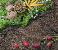 New design. Christmas design. On the table lay sacking tangerines, berries, branch of pine or spruce cones. Blank space for writin Royalty Free Stock Photo
