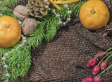 New design. Christmas design. On the table lay sacking tangerines, berries, branch of pine or spruce cones. Blank space for writin Royalty Free Stock Photos