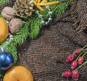 New design. Christmas design. On the table lay sacking tangerines, berries, branch of pine or spruce cones. Blank space for writin Stock Image