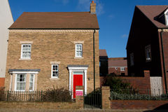 New detached house with red door. New housing estate in Swindon, Wiltshire, UK. Rather than having houses built in the same style, modern luxury estates utilise Royalty Free Stock Images