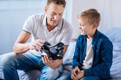 Pleasant father showing his son new VR headset. New device. Charming upbeat men sitting on the bed next to his pre-teen son and showing him their new VR headset Stock Image