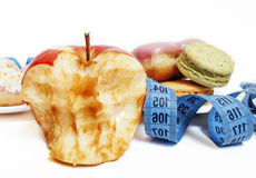 New diet concept, question sign in shape of measurment tape between red apple and donut isolated on white Royalty Free Stock Photography