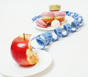 New diet concept, question sign in shape of measurment tape between red apple and donut isolated on white Royalty Free Stock Photos
