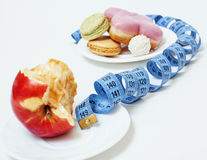 New diet concept, question sign in shape of measurment tape between red apple and donut isolated on white Stock Photo