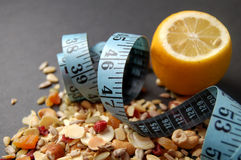 New Dieting. This is an image of a lemon, measuring tape and some country mix fruit/cereal Stock Image