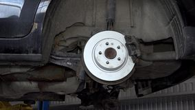 New disc brake and wheel hub. Car hanging on elevator in garage. Zoom in stock video