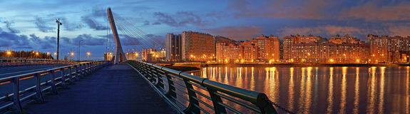 New districts of the big city. Stitched Panorama cable-stayed bridge and the modern night city at the lake Royalty Free Stock Images