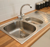 New Domestic Kitchen Sink. Stainless steel sink with mixer tap recessed into worktop Royalty Free Stock Photos