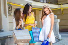 New dress. Girls holding shopping bags and walk around the shops Royalty Free Stock Photos