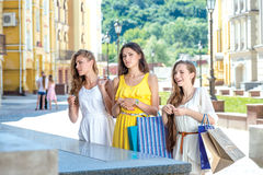 New dress at shop window. Girls holding shopping bags and walk a Royalty Free Stock Image
