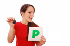 New driver. Girl who has just passed test holding car key and P plate on white isolated background Stock Image