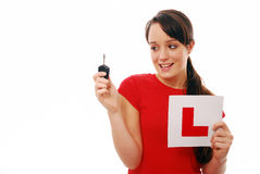 New driver. Proud girl looking at car key and L plate on white isolated background Stock Photos