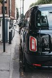 New electric LEVC TX London black cab charging from changing point in London, UK. New electric LEVC TX London black cab charging from changing point on a street stock image
