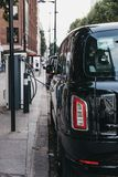 New electric LEVC TX London black cab charging from changing point in London, UK. New electric LEVC TX London black cab charging from changing point on a street royalty free stock photography