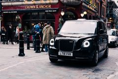 New electric LEVC TX London black cab on a street in Covent Garden, London, UK. First electric taxis started operating in London in January 2018 stock photos