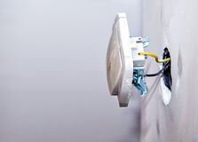 New electrical installation. Power switch socket and electrical cables on the wall, renovation concept closeup Stock Image