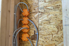 New electrical installation, socket plastic boxes and electrical. Cables on the wall, renovation concept. Electrical wiring installation Stock Image
