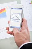 New email message icon on a mobile phone. Held in the hand of a businessman as he checks his mail at work Royalty Free Stock Image