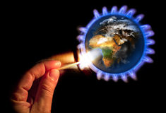 New energy for the planet. Man hand lighting a stove with watermarks on the planet Royalty Free Stock Images