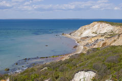 New England Beach. A scenic view of Aquinnah, or Gayhead Beach in Martha's Vineyard. Clay sea cliffs with green brush meet the blue sea with a partly cloudy sky Stock Photo