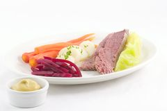 New England boiled dinner. Corned beef,cabbage,whole carrots, potatoes and beets artfully arranged on a white plate with mustard on the side royalty free stock photos