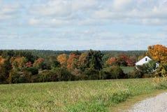 New England fält på en ljus solig mitt--Oktober dag Vitt lantgårdhus och träd som vänder färger i avstånd Royaltyfri Foto