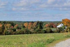 New England fält på en ljus solig mitt--Oktober dag Vitt lantgårdhus och träd som vänder färger i avstånd Royaltyfria Foton