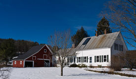 New England Farm House Barn. A classic white clapboard New England farm house in winter complete with apple tree in front, American flag on the porch and Royalty Free Stock Images