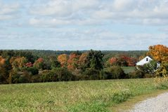 New England field on a bright sunny mid-October day. White farm house and trees turning colors in distance. Yellow red green orange leaves blue sky puffy white Royalty Free Stock Photo